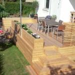 Færdig terrasse med let afskærmning som blomsterkasser og smalt plankeværk.